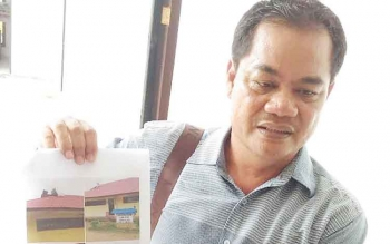 Anggota DPRD Kabupaten Gunung Mas Untung Jaya Bangas memperlihatkan foto bangunan SD di Desa Tanjung Untung, Kecamatan Tewah, yang rusak.