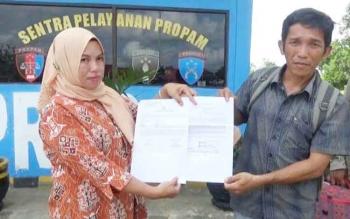 Arlena didampingi mantir adat Desa Mangkahui menunjukan surat laporan mereka atas dugaan penganiayaan terhadap anaknya oleh jajaran Polsek Mura kepada Propam Polres Mura, Rabu (12/4/2017).