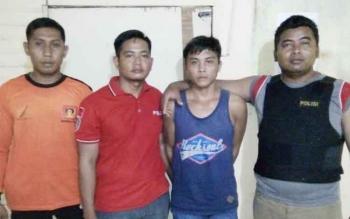 Banjir (24), tersangka pembunuhan (kaos biru) diamankan anggota Polsek Antang Kalang, Rabu (12/4/2017).
