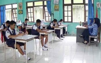 Dua orang guru sedang mengawasi puluhan siswa yang mengikuti USBK di SMPN 1 Sampit, Senin (17/4/2017).
