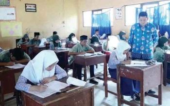 Kepala MTs Annur Palangka Raya Rus'ansyah memantau peserta didik kelas IX yang sedang menjalani try out menjelang ujian nasional madrasah berstandar nasional (UAMBN).