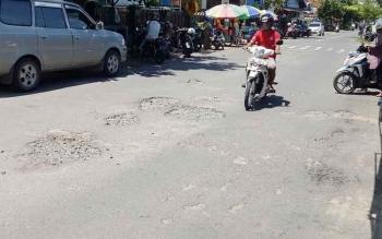Pengendara bermotor tengah melintasi salah satu bagian ruas Jalan MT Haryono Kuala Pembuang yang berlubang.