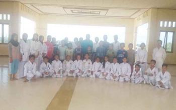 sejumlah generasi muda yang berlatih bela diri karate dan pelatih saat berfoto bersama.