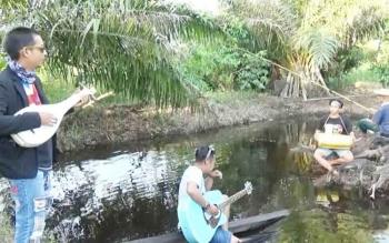 Nirwansyah (bertopi caping) saat berkolaborasi menyanyikan syair diiringi dambus di tengah kolam ikan di Jalan Kotawaringin Lama.