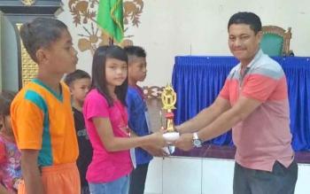 Ketua panitia O2SN SD tingkat Kabupaten Gunung Mas Cendrawan menyerahkan piala kepada juara cabor renang saat acara penutupan di GPU Tampung Penyang, Kuala Kuru, Selasa (18/4/2017).