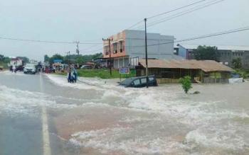 Sebuah mobil tersweret arus banjir di Kecamatan Pangkalan Banteng, belum lama ini.