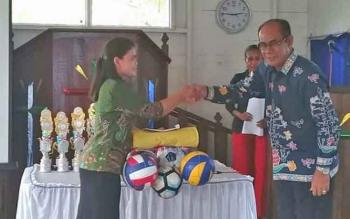Kepala Disparpora Gunung Mas (Gumas) Suprapto Sungan menyerahkan bola voli dan net saat menghadiri HUT GKE ke-178 di Tumbang Napoi, Kecamatan Miri Manasa (18/4/2017).