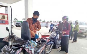 Petuas SPBU saat melayani pelanggan menggunakan Baju Batik.
