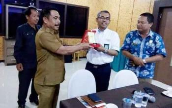 Ketua Komisi I DPRD Gunung Mas Helprit Tiong didampingi anggota DPRD Iswan B Guna dan Polie L Mihing menyerahkan cendera mata kepada Genderal Manager PLN Kalteng-Kalsel.