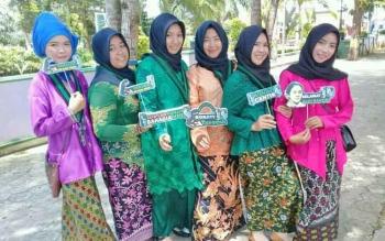 Anggota KOHATI dan kader HMI foto bersama seusai membagikan bunga dan brosur mengenai stop kekerasan terhadap perempuan dan anak kepada pengendara