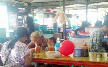 Para pengunjung menikmati makanan di warung bawah jembatan Kahayan, Palangka Raya, Sabtu (22/4/2017).