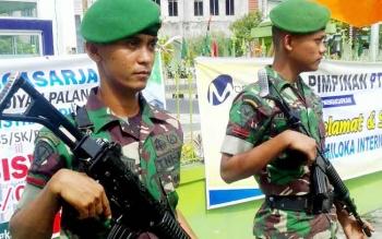 Aparat bersenjata dari TNI berjaga di Jalan RT A Milono.