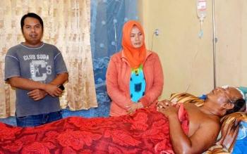 Rusminiati (berjilbab) saat menengok suaminya, Danuri, yang dirawat di RSUD Muara Teweh, Kabupaten Barito Utara.