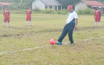 Kepala Dinas Pariwisata Pemuda dan Olahraga Kabupaten Gunung Mas Suprapto Sungan menendang bola tanda dimulainya turnamen sepak bola piala Kepala Desa Tumbang Miwan atau Kades Cup 2017.