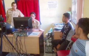 Kepala Dinas Kependudukan dan Catatan Sipil Barito Selatan, Nyamei Tumbai (kiri), sedang mengawasi proses cetak KTP elektronik.