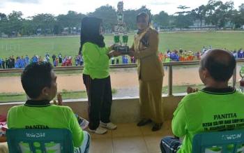 Kepala keolah yang menjadi juara umum O2SN 2016 menyerahkan piala bergilir kepada ketua panitia O2SN
