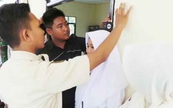 Seorang siswa sedang mengikuti seleksi tinggi badan mereka saat mengikuti seleksi paskibraka.