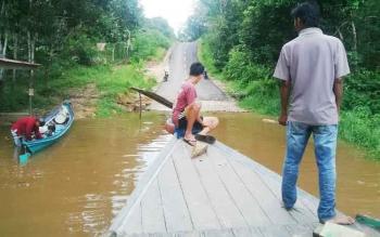 Jalan dari Desa Muara Untu menuju Kota Puruk Cahu, Kabupaten Murung Raya, terendam karena meluapnya air Sungai Barito, Selasa (25/4/2017).