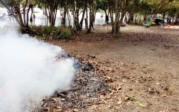 Tumpukan sampah daun kering yang dibakar oleh petugas kebersihan di lokasi wisata air Danau Seluluk, Desa Derangga, Kecamatan Hanau.