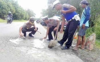 Kapolres Pulang Pisau AKBP Dedy Sumarsono dan Kasat lantas AKP A. Wakid, saat menambal lubang di badan jalan lintas kalimantan.