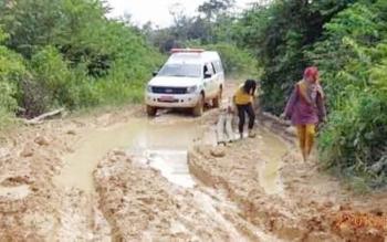Ambulans melintas di jalan berlumpur. Sejumlah desa di Kotawaringin Barat kekurangan tenaga pendidik dan tenaga kesehatan.