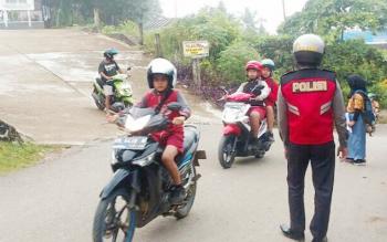 Sejumlah murid SD mengendarai sepeda motor tampak santai melewati polisi yang berjaga.