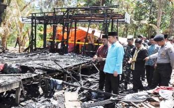 Bupati Kapuas Ben Brahim S Bahat didampingi Lurah Panamas Slamet Riyadi dan pihak kepolisian dan Koramil Selat saat meninjau rumah Rasid Arianto yang terbakar, Minggu (30/4/2017).