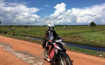 Salah satu pengendara sepeda motor melintas di jalan poros Desa Tanjung Terantang yang hanya menyisakan sebagian aspal saja.