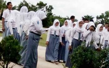 Sejumlah Siswa kelas XII SMAN 1 Sematu Jaya saat menanti pengumuman kelulusan di halaman sekolah.