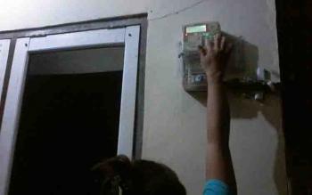Warga memeriksa meteran listrik di rumahnya.