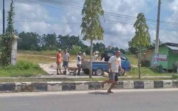 Mobil bak terbuka dari Dinas Pekerjaan Umum Kotawaringin Barat, Kamis (4/5/2017) pagi, menurunkan pekerja untuk memperbaiki Jalan Ahmad Yani, Kelurahan Baru, Pangkalan Bun. Kemarin pagi lobang di jalan ini membuat seorang perempuan terjatuh dari sepeda m
