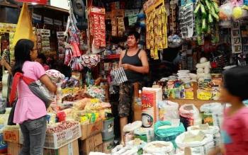 Seorang ibu sambil menggendong anaknya sedang berbelanja di Pasar Kahayan, Palangka Raya