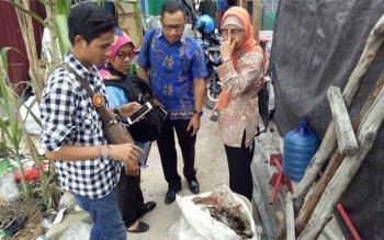 Petugas BPOM sedang memeriksa sebuah karung beras berisi bekas bahan untuk pembuatan jamu madu klanceng, saat penggerebekan pabrik jamu ilegal.
