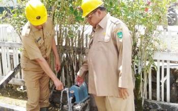 Bupati Sukamara, Ahmad Dirman didampingi wakilnya Windu Subagio saat mencoba dan mengecek aliran air yang disuplai ke rumah masyarakat.