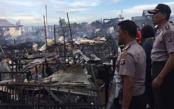 Polres Palangka Raya dan Polsek Pahandut memasang garis polisi di lokasi kebakaran Gang Kencana, Jalan Kalimantan, Palangka Raya, sekitar pukul 07.00 WIB, Selasa (9/5). Dari data yang dicek kepolisian ada sekitar 30 rumah terbakar.