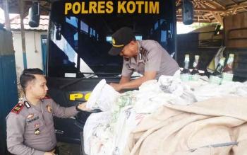 Kapolsek KPM Iptu Triono bersama seorang anggotanya sedang membuka penutup pikap yang mengangkut jamu ilegal, Selasa (9/5/2017)