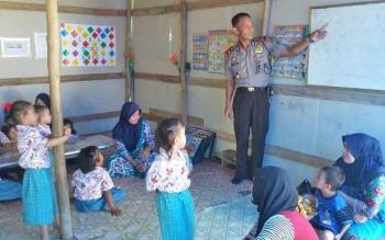 Kapolsek Basarang, AKP Darwin saat mengajar anak-anak PAUD Permata Hati Bunda.