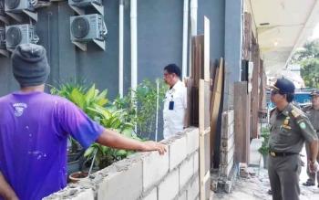 Kepala DPPMTPSP Johny Tangkere dan Satpol PP meminta tembok dibangun di Jalur Hijau agar dibongkar.
