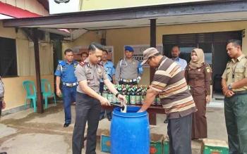Kapolsek KPM Iptu Triono Raharjo bersama pemilik jamu ilegal melakukan pemusnahan jamu tersebut dengan cara dipecahkan botolnya, Rabu (10/5/2017).