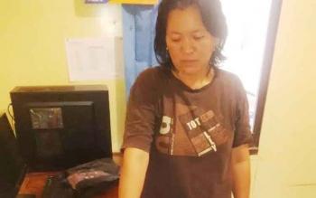 Ibu rumah tangga penjual zenith bernama Rusna Ningsih berdiri di samping meja tempat polisi membeberkan barang bukti yang berhasil diamankan.