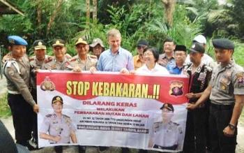 Menteri Lingkungan Hidup dan Kehutanan Siti Nurbaya bersama aparat kepolisian dan rombongan membentangkan spanduk stop kebakaran saat berkunjung ke Borneo Orangutan Survival Foundation di Nyaru Menteng, Palangka Raya, Jumat (12/5/2017) sore.