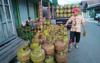 Pekerja tengah menurunkan tabung gas LPG 3 kg di sekitar Pelabuhan Kasongan Kabupaten Katingan untuk dikirim ke wilayah pelosok, Minggu (14/5/2017)