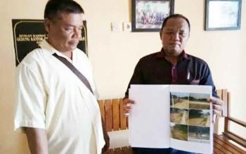 Hendri dan seorang anggota keluarga memerlihatkan foto-foto lahan mereka yang diduga dirusak kontraktor Jembatan Kalanaman dan DPU di Kantor PWI Katingan, Senin (15/5/2017).