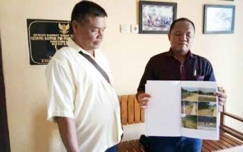 Hendri dan keluarganya menunjukkan foto-foto lahan mereka yang diduga dirusak kontraktor pembangunan Jembatan Kalanaman di Kantor PWI Katingan, Senin (15/5/2017).