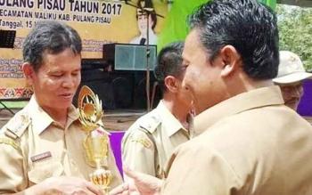 Bupati saat menyerahkan piala dan piagam penghargaan kepada camat dan kepala desa yang berhasil dalam pembangunan kecamatan dan desa pada acara BBGRM di Desa Sidodadi.