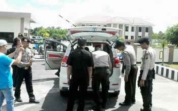 Suasana depan pintu masuk PN Kasongan tampak anggota Polres Katingan tengah memeriksa warga yang hendak menghadiri sidang perdana gugatan Ahmad Yantenglie, Selasa (16/5/2017)