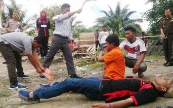 Salah satu adegan rekonstruksi kasus pembunuhan sadis di Desa Batu Belaman. Rekonstruksi tersebut tidak dihadiri saksi utama (Sri Utami).
