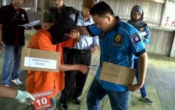 Tersangka AC memperagakan caranya menusuk korban Wahyu Priyanto saat rekonstruksi di kompleks Perumahan Betang, Jalan Temanggung Tilung, Palangka Raya, Selasa (16/5/2017).