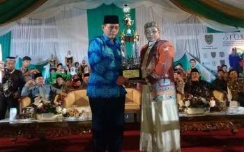 Wakil Gubernur Kalteng Habib Haji Said Ismail menyerahkan piala juara STQ Tingkat Provinsi Kalteng Ketua LPTQ Kabupaten Kotim, H. Sugianoor saat malam penutupan, Rabu (17/5/2017) malam.
