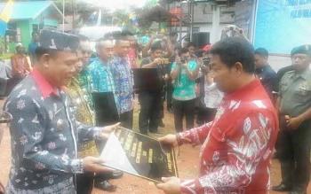 Bupati Ahmad Yantenglie menyerahkan plakat pencanangan kampung KB kepada 5 camat di Katingan, tampak Camat Tasik Payawan menerima plakat dari Bupati Ahmad Yantenglie